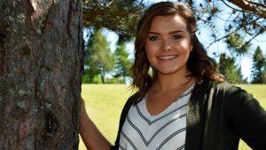 female student posing next to tree