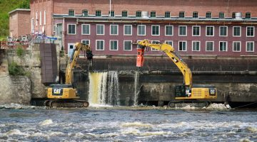 heavy equipment deconstructing a dam