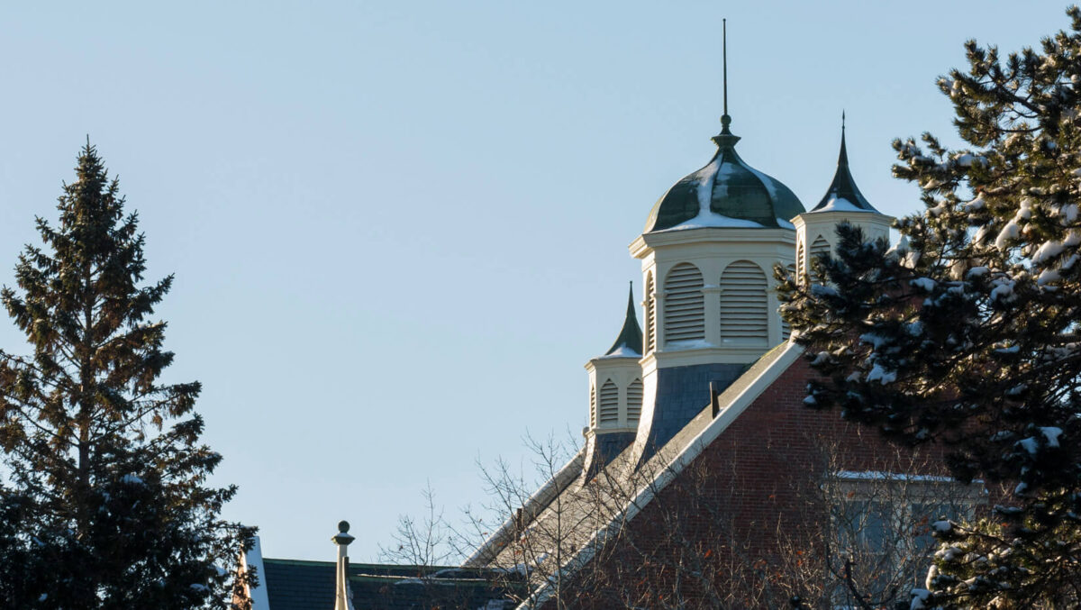 Part of the roof of Winslow Hall with a little snow framed by trees