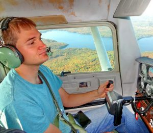 Elias Ayrey flying a small plane over Maine
