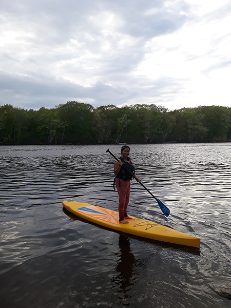 Morelys Rodriguez on a standup paddle board on the Stillwater River